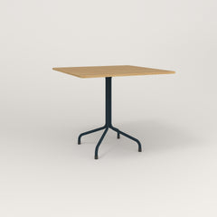RAD Cafe Table, Rectangular 4 Top Tube Four Point Base in white oak europly and navy powder coat.