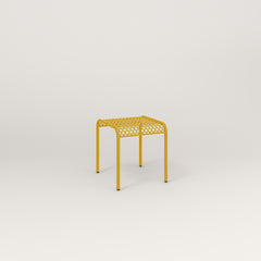 RAD Signature Bent Tube Stool in perforated steel and yellow powder coat at dining height.