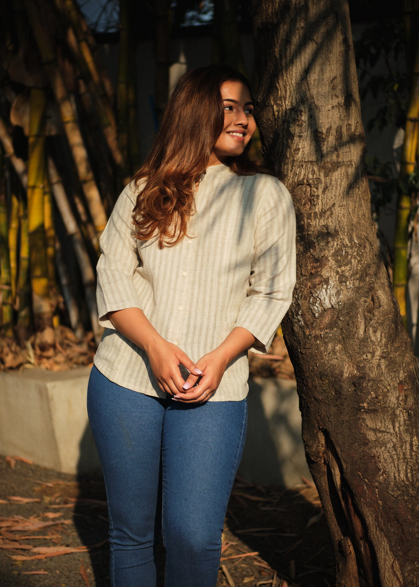 woman in a beige shirt leaning against a tree