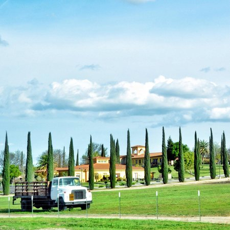 Daytime photo of Broken Earth Winery featuring large house and truck