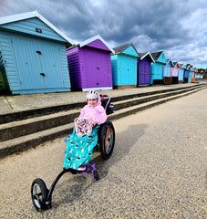 Carmela Chillery Watson in front a row of colourful beach huts, wearing a pink hoodie and seagull print BundleBean wheelchair cosy