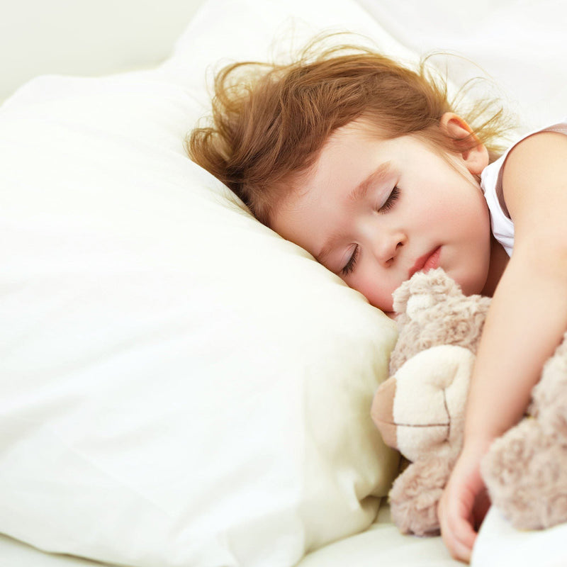 Baby girl sleeping on a ivory pillow case hugging a teddy bear