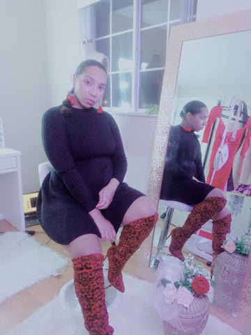 Black ribbed sweater  mini dress . Red thigh-high stiletto boots