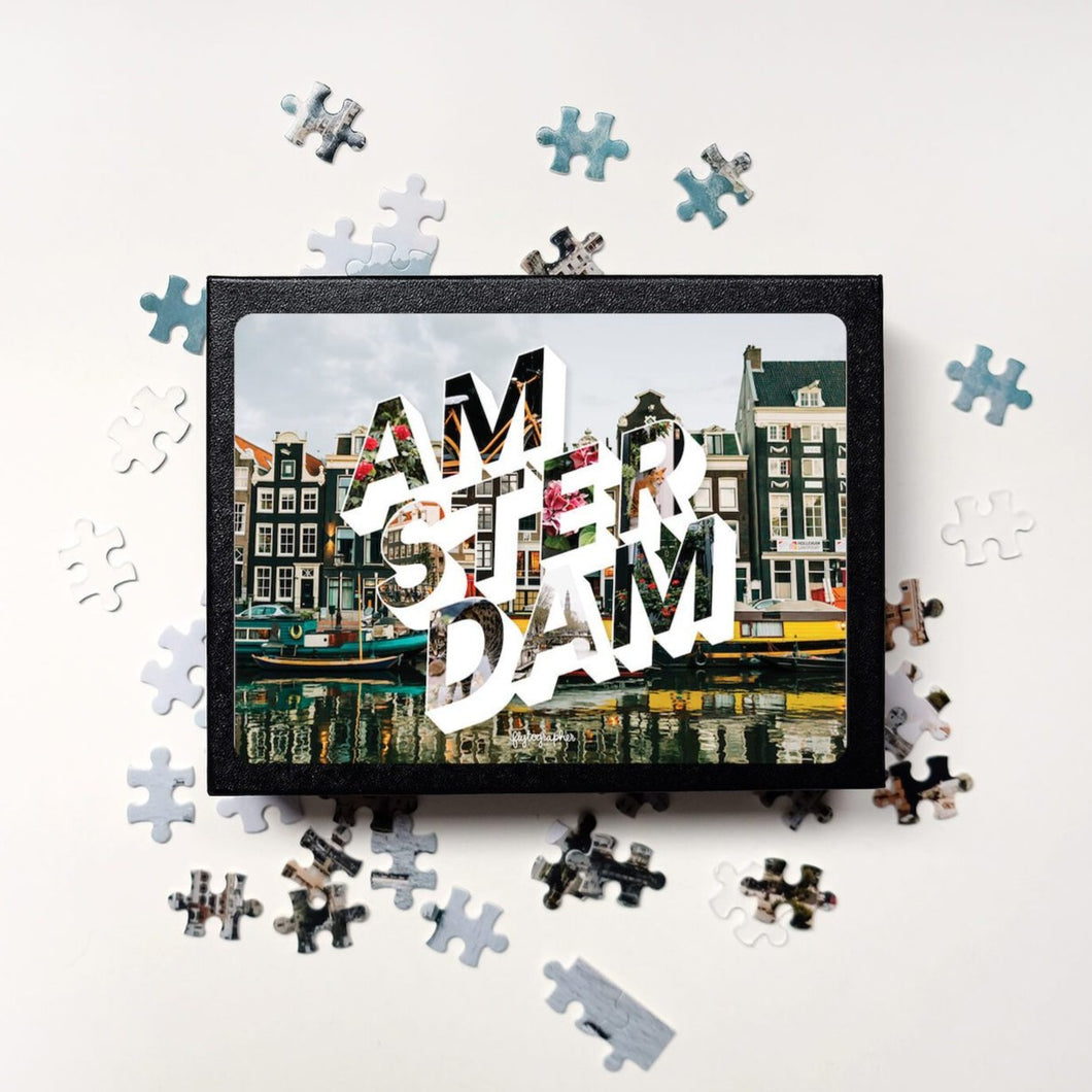 Puzzle of a picture of Amsterdam that comes in a black box. Medium, 252-piece puzzle measures 14 inches by 10 inches and has a glossy finish. It comes in a black box with a 5 x 7 print of the image on top of the box. Box measures 5.625