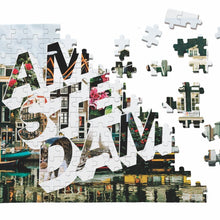 "Load image into Gallery viewer, Puzzle of a picture of Amsterdam that comes in a black box. Medium, 252-piece puzzle measures 14 inches by 10 inches and has a glossy finish. It comes in a black box with a 5 x 7 print of the image on top of the box. Box measures 5.625"" x 7.625"" x 1.2""."