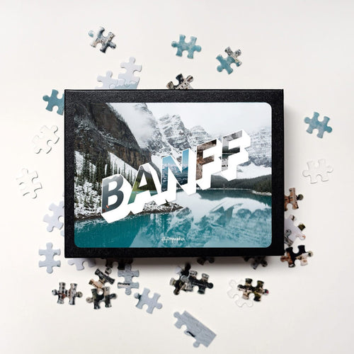 Puzzle of a picture of Banff comes in a black box. Medium, 252-piece puzzle measures 14 inches by 10 inches and has a glossy finish. It comes in a black box with a 5 x 7 print of the image on top of the box. Box measures 5.625