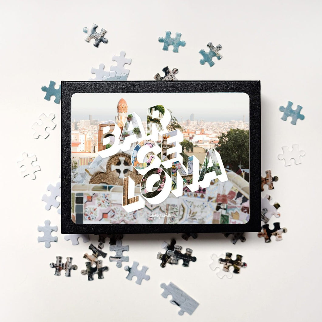 Puzzle of a picture of Barcelona comes in a black box. Medium, 252-piece puzzle measures 14 inches by 10 inches and has a glossy finish. It comes in a black box with a 5 x 7 print of the image on top of the box. Box measures 5.625