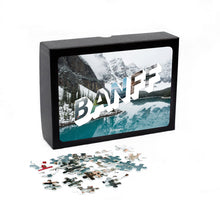 "Load image into Gallery viewer, Puzzle of a picture of Banff comes in a black box. Medium, 252-piece puzzle measures 14 inches by 10 inches and has a glossy finish. It comes in a black box with a 5 x 7 print of the image on top of the box. Box measures 5.625"" x 7.625"" x 1.2""."