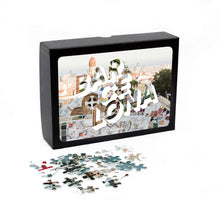 "Load image into Gallery viewer, Puzzle of a picture of Barcelona comes in a black box. Medium, 252-piece puzzle measures 14 inches by 10 inches and has a glossy finish. It comes in a black box with a 5 x 7 print of the image on top of the box. Box measures 5.625"" x 7.625"" x 1.2""."