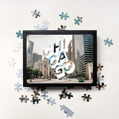 Puzzle of a picture of Chicago comes in a black box. Medium, 252-piece puzzle measures 14 inches by 10 inches and has a glossy finish. It comes in a black box with a 5 x 7 print of the image on top of the box. Box measures 5.625