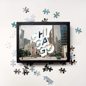 "Puzzle of a picture of Chicago comes in a black box. Medium, 252-piece puzzle measures 14 inches by 10 inches and has a glossy finish. It comes in a black box with a 5 x 7 print of the image on top of the box. Box measures 5.625"" x 7.625"" x 1.2""."