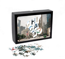 "Load image into Gallery viewer, Puzzle of a picture of Chicago comes in a black box. Medium, 252-piece puzzle measures 14 inches by 10 inches and has a glossy finish. It comes in a black box with a 5 x 7 print of the image on top of the box. Box measures 5.625"" x 7.625"" x 1.2""."