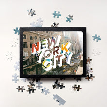 Load image into Gallery viewer, Medium, 252-piece puzzle measures 14 inches by 10 inches and has a glossy finish. It comes in a black box with a 5 x 7 print of the image on top of the box of New York City.