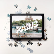 Load image into Gallery viewer, Medium, 252-piece puzzle measures 14 inches by 10 inches and has a glossy finish. It comes in a black box with a 5 x 7 print of the image of Paris on top of box.