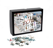 Load image into Gallery viewer, Medium, 252-piece puzzle measures 14 inches by 10 inches and has a glossy finish. It comes in a black box with a 5 x 7 print of the image on top of the box of Santorini