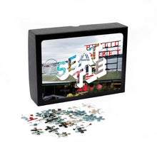 Load image into Gallery viewer, Medium, 252-piece puzzle measures 14 inches by 10 inches and has a glossy finish. It comes in a black box with a 5 x 7 print of the city image of Seattle on top of box.