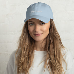 Model is wearing a light blue baseball cap that has a low profile with an adjustable strap and curved visor.