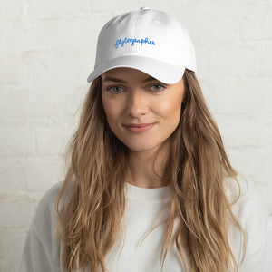 woman is wearing 100% Chino cotton twill baseball cap that hat has a low profile with an adjustable strap and curved visor.