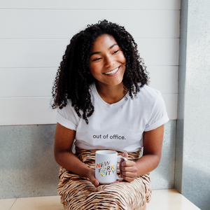 woman is wearing a white 100% cotton t-shirt with the words 'out of office' written on front