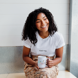 woman is wearing a white 100% cotton t-shirt with the words road trip on it in black and holding a white ceramic mug with Seattle written on front.