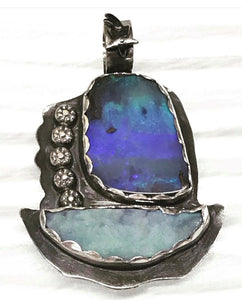 this boulder opal pendant is handmade to look like a sailboat.  I think of it as sailing away in a night sky because it is oxidized sterling silver to represent the night sky.