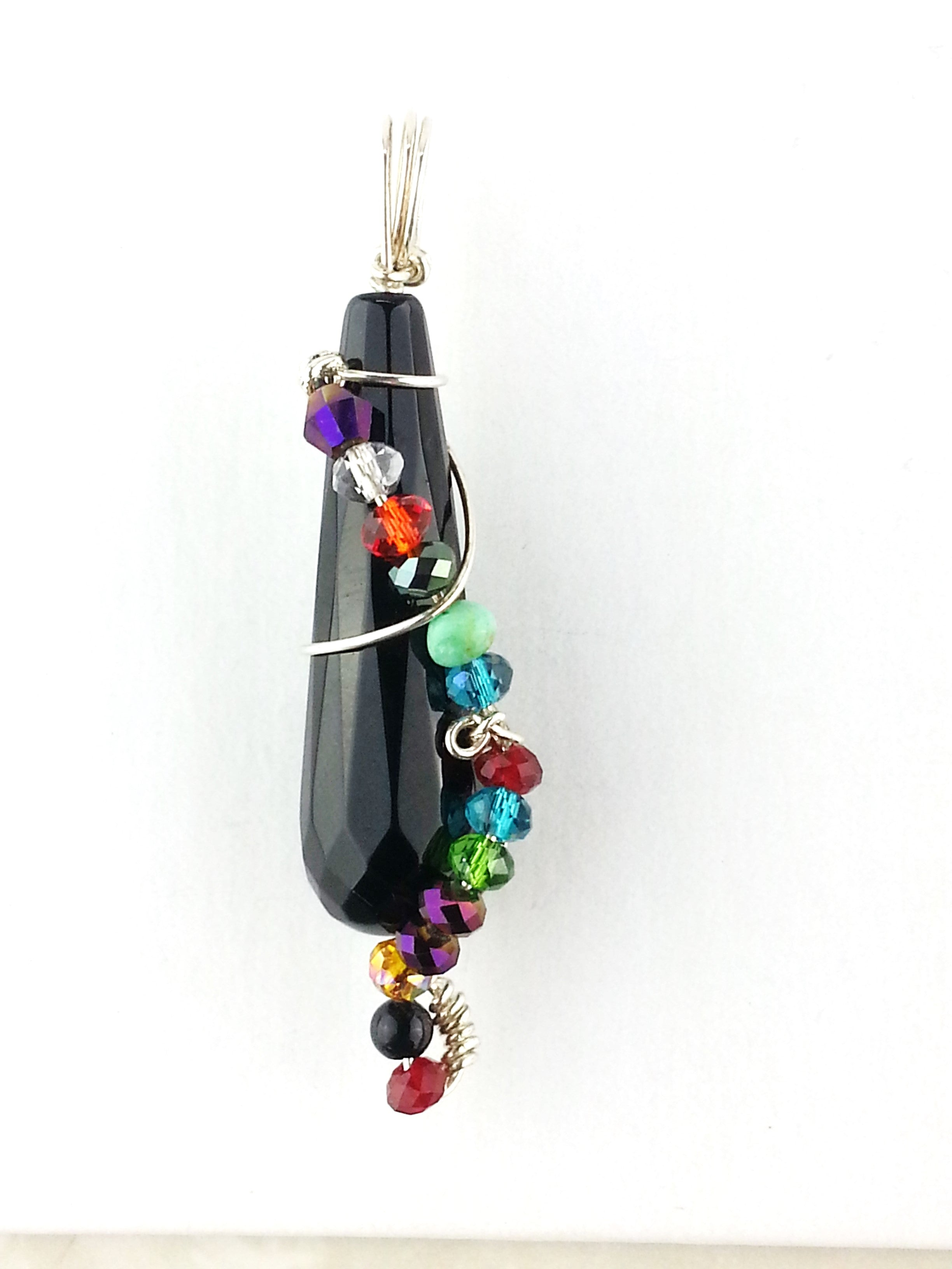 Teardrop black onyx pendant delicately wrapped in gold with a rope look of colorful ball shaped crystals.