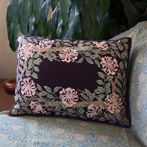 Honeysuckle Border stitched as a cushion with a mauve background