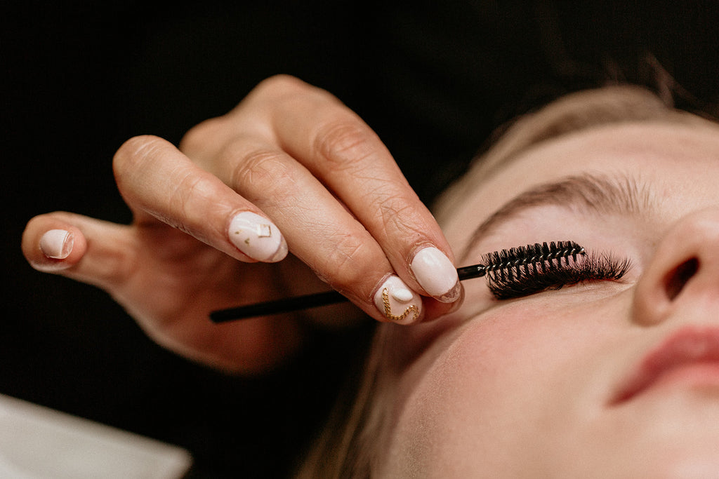 Lash artist brushing client's lashes