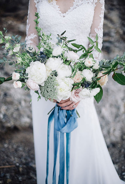 White bouquet with blue ribbon