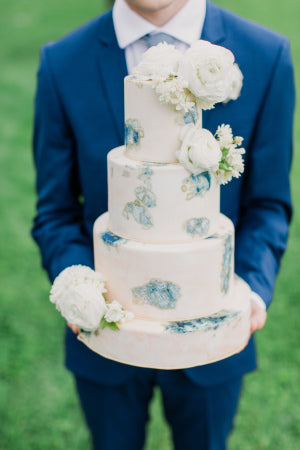 White wedding cake with flowers and blue accents