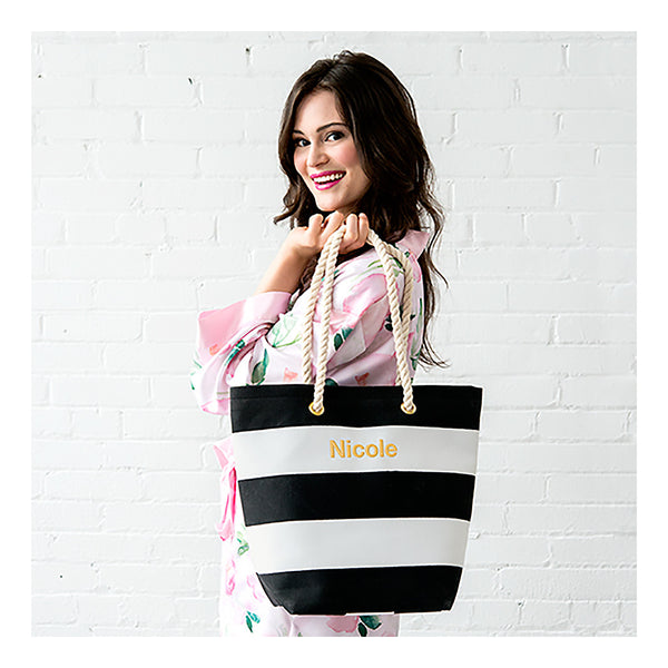 Model holding black and white stripe tote bag