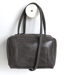 Tuesday. small frrry bag. shoulder bag. hand-held-bag. evening bag. thin strap. zipper closure. piombo colour. grey. suede