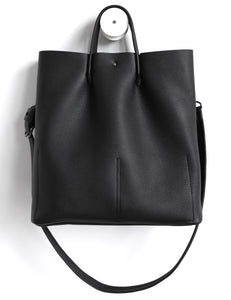 Monday frrry tote bag. shoulder strap. black. back view. button closure