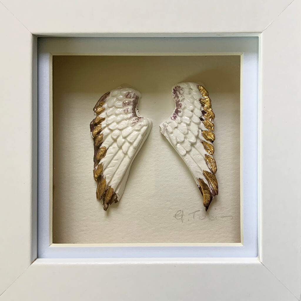Angel Wings by Heather Tobias is a handmade porcelain and gold lustre ceramic artwork presented in a white or grey frame