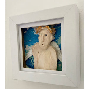 Guardian Angel 3 by Heather Tobias is a porcelain and underglazed celestial being on a marbled acrylic background in a light grey frame side