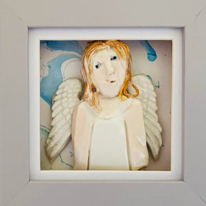 Guardian Angel 6 by Heather Tobias is a porcelain and underglazed celestial being on a marbled acrylic background in a light grey frame.