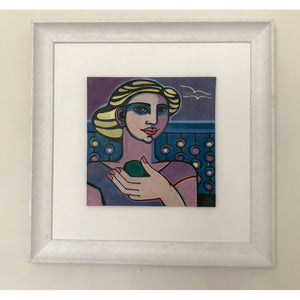 Glazed earthenware ceramic hand painted tile of a woman with painted nails holding a piece of sea glass by artist Linda Samson on wall