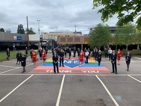 a photograph of various airline staff standing in a carpark on top of a big blue heart with a rainbow background which says NHS and Thank you