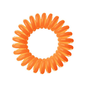 An orange coloured plastic spiral circular hair bobble on a white background called a spirabobble.