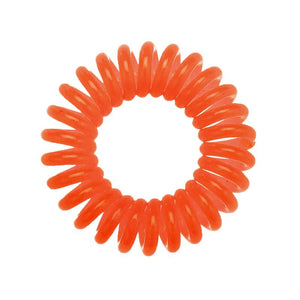 A bright orange coloured plastic spiral circular hair bobble on a white background called a spirabobble.