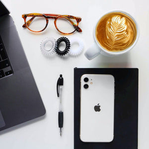 Aerial picture of a desk with laptop, iphone, notepad, a latte coffee, brown specs and a black spirabobble