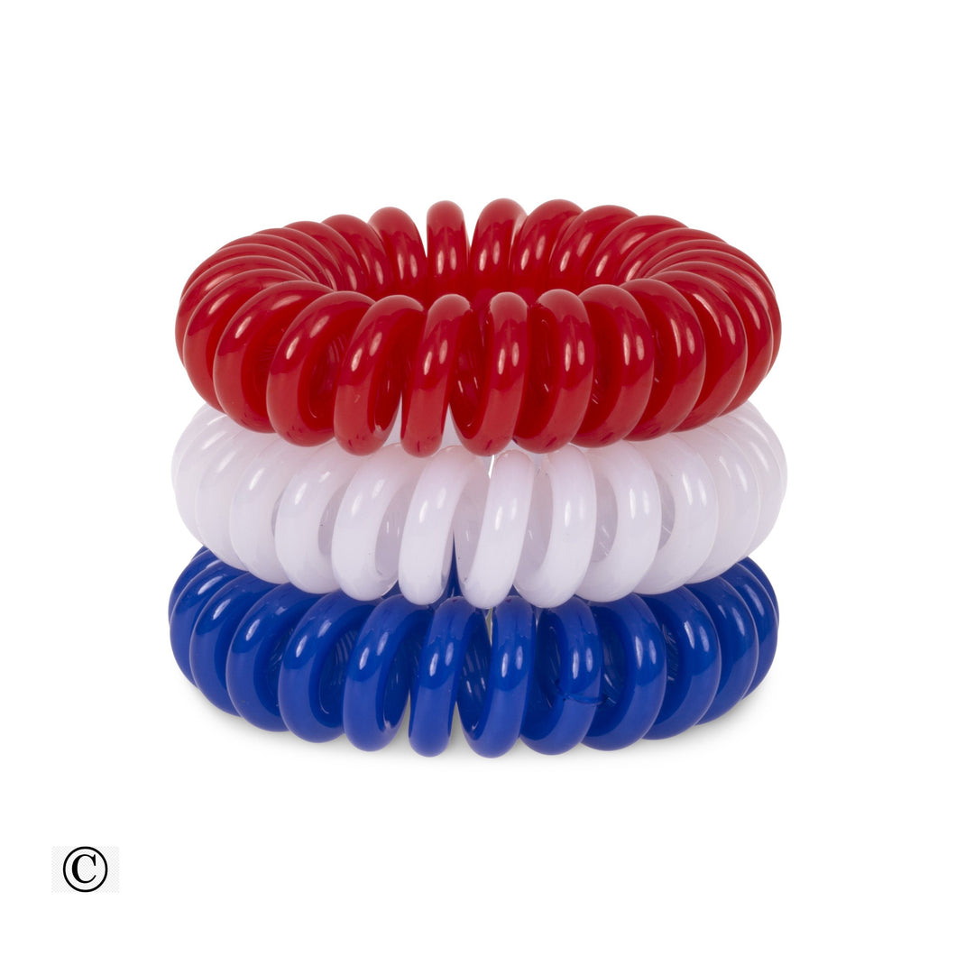 A tower of three (placed on top of each other) of solid red, white and blue coloured plastic spiral circular hair bobbles on a white background that looks like an old fashioned curly coiled telephone cable or a coiled spring which has been made into a cir