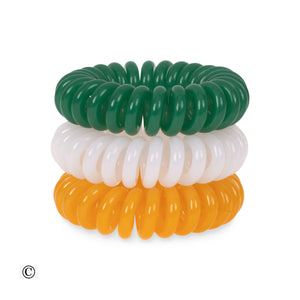 A tower of three (placed on top of each other) of green, white and orange coloured plastic spiral circular hair bobbles on a white background that looks like an old fashioned curly coiled telephone cable or a coiled spring which has been made into a circu