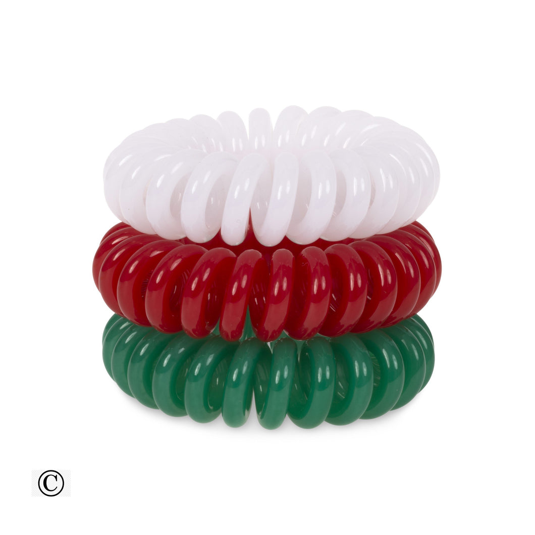A tower of three (placed on top of each other) of white, red and green coloured plastic spiral circular hair bobbles on a white background that looks like an old fashioned curly coiled telephone cable or a coiled spring which has been made into a circular