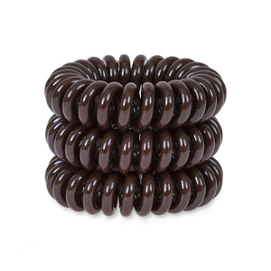 A tower of 3 brown sugar coloured hair bobbles called spirabobbles. A plastic spiral circular hair tie spira bobble.