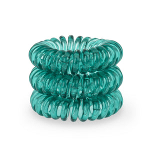 A tower of 3 serene green coloured hair bobbles called spirabobbles. A plastic spiral circular hair tie spira bobble.