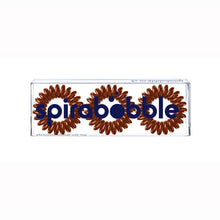 Load image into Gallery viewer, A flat transparent box of 3 cinnamon bun brown coloured hair accessories called spirabobbles