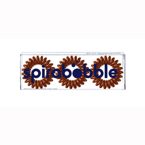 A flat transparent box of 3 cinnamon bun brown coloured hair accessories called spirabobbles