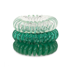 A tower of 3 clearly green coloured hair bobbles called spirabobbles. A clear and green plastic spiral circular hair tie spira bobble.