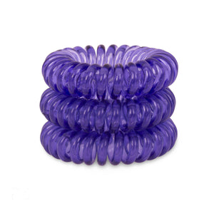 A tower of 3 deep purple coloured hair bobbles called spirabobbles. A purple plastic spiral circular hair tie spira bobble